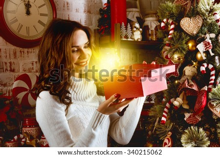 Beautiful girl holds red box with magic present staying on christmas tree backdrop - stock photo