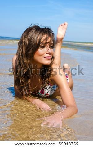 Beautiful girl in a bikini lies on the beach in the water - stock photo