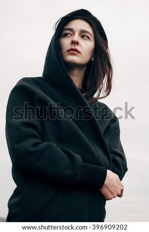 Beautiful girl in a black cloak against the gray sky - stock photo