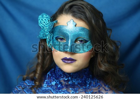 Beautiful girl in a blue carnival mask, close-up portrait  - stock photo