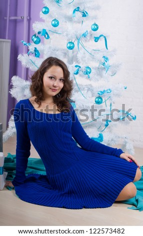 beautiful girl in a blue dress near white Christmas tree