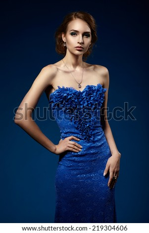 Beautiful girl in a blue evening dress on a blue background. - stock photo