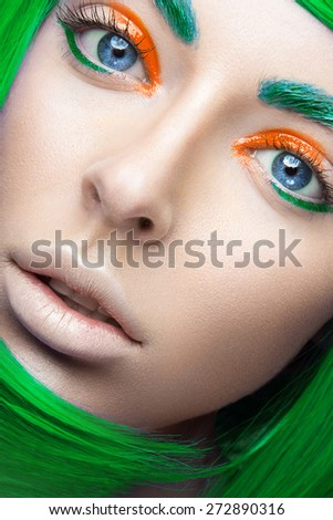Beautiful girl in a bright green wig in the style of cosplay and creative makeup. Beauty face. Art image. Picture taken in the studio on a yellow background. - stock photo
