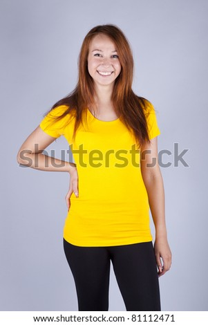 beautiful girl in a bright yellow T-shirt stands on a gray background - stock photo