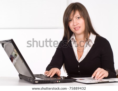 beautiful girl in a business suit working in the office