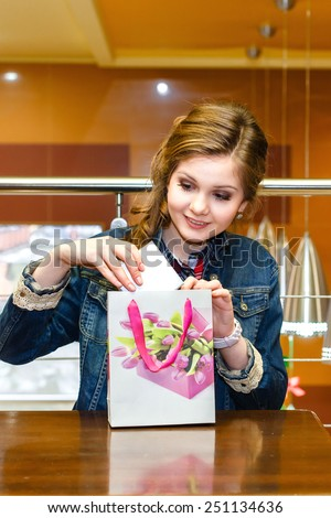 Beautiful girl in a cafe pulled out a white gift box - stock photo