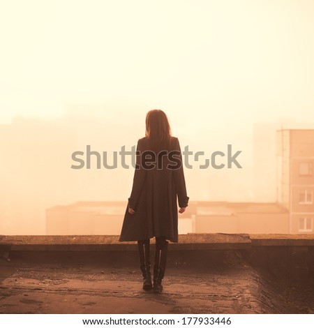 beautiful girl in a coat on a rooftop in the city. morning photo - stock photo