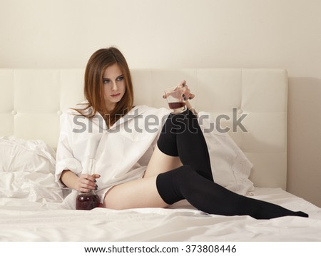 beautiful girl in a depression in the white bedroom drink alcohol - stock photo