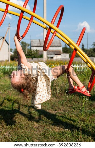 Beautiful girl in a dress hanging on the playground rings