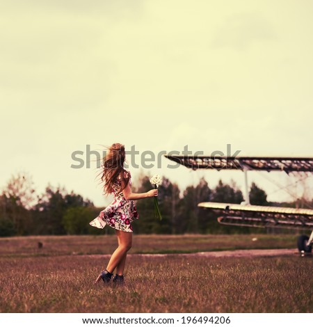 Beautiful girl in a dress in the wind in a field of flowers around the aircraft - stock photo