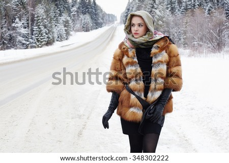 beautiful girl in a fur coat waiting for the car on a winter road in the forest.young Woman in fashionable Fur Coat,leather gloves and scarf. snow time - stock photo