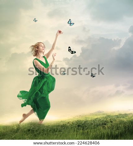 Beautiful girl in a green dress following butterflies on a mountain  - stock photo