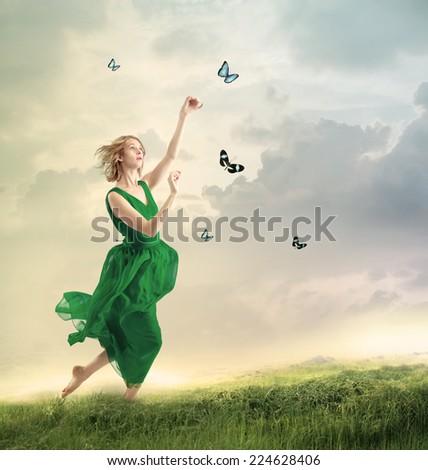 Beautiful girl in a green dress following butterflies on a mountain  - stock photo