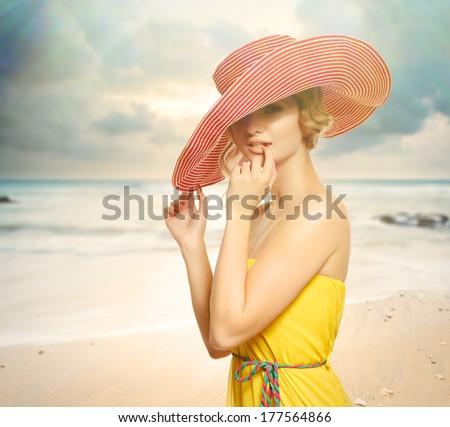 Beautiful girl in a hat enjoying the sun on the beach - stock photo