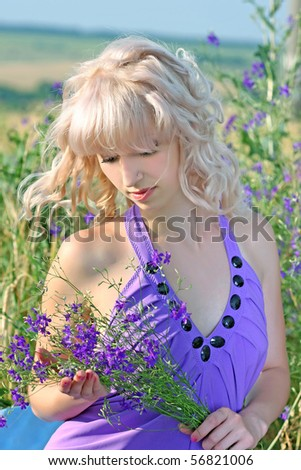 beautiful girl in a lavender dress with a bouquet of flowers in a field - stock photo