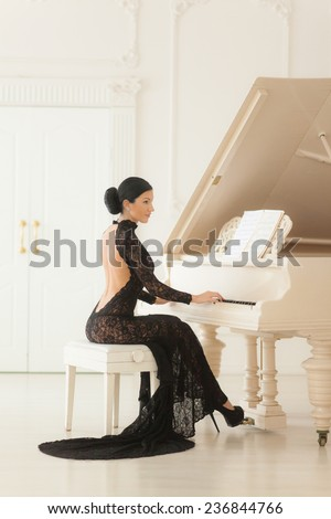 Beautiful girl in a long black dress sitting at the piano. - stock photo
