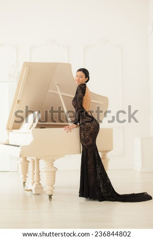 Beautiful girl in a long black dress standing at the piano. - stock photo