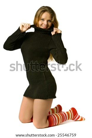 beautiful girl in a long sweater and coloured golfs stands on knees, isolated on white