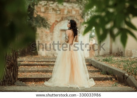 Beautiful girl in a luxurious dress walks in autumn park near the castle.Princess  on the steps of the fall of the castle.Fashionable toning.creative colors - stock photo