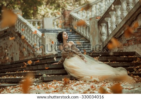Beautiful girl in a luxurious dress walks in autumn park near the castle.Princess sits on the steps of the fall of the castle.Fashionable toning.?reative colors - stock photo