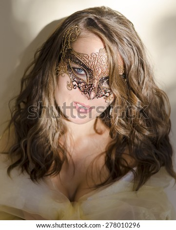Beautiful girl in a mask with long hair at sunset