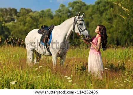 Beautiful girl in a pink dress walks with a horse on a meadow - stock photo