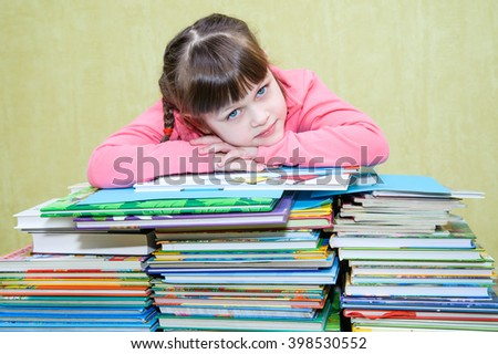 Beautiful girl in a pink jacket hid behind a stack of books - stock photo