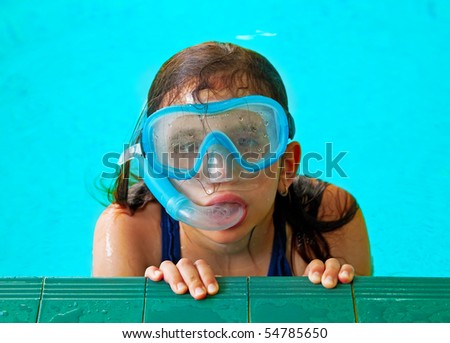 Beautiful girl in a pool with a swimming mask and snorkel - stock photo