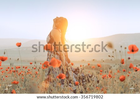 beautiful girl in a poppy field at sunset. concept of freedom - stock photo