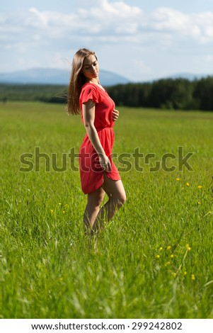 Beautiful girl in a red dress in a field on a sunny day - stock photo
