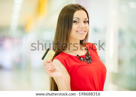 Beautiful girl in a red dress with long hair shopping, smiling and holding a credit card
