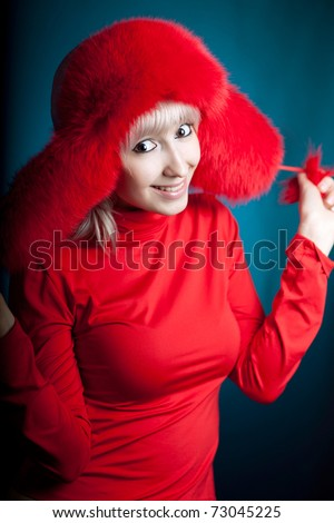 beautiful girl in a red fur hat on a blue background - stock photo