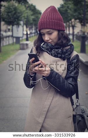 Beautiful girl in a red hat and coat carefully read the message on the phone and listening to music. - stock photo