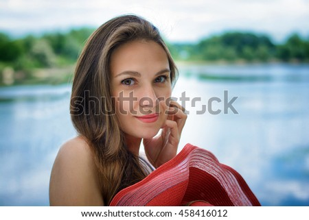 Beautiful girl in a red hat smiling at the summer waterfront - stock photo