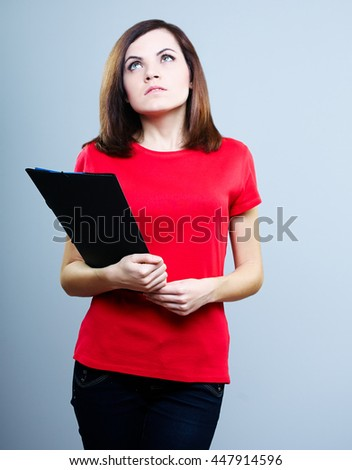 beautiful girl in a red T-shirt and jeans holding a folder and looking at the top, on a gray background - stock photo