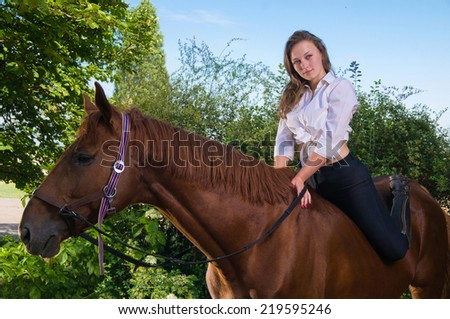 beautiful girl in a shirt and a horse near the tree