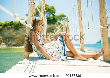 Beautiful girl in a summer dress. girl sitting on a bridge. beautiful teen girl in a dress with long hair and sunglasses sitting on the bridge in summer