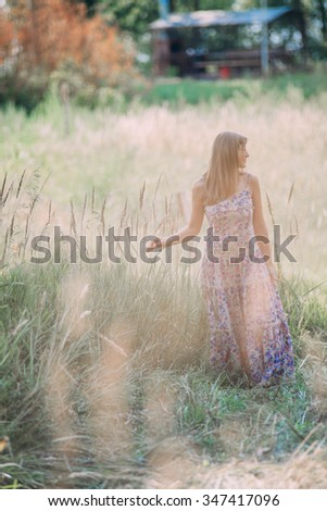 beautiful girl in a summer dress walking in the woods - stock photo