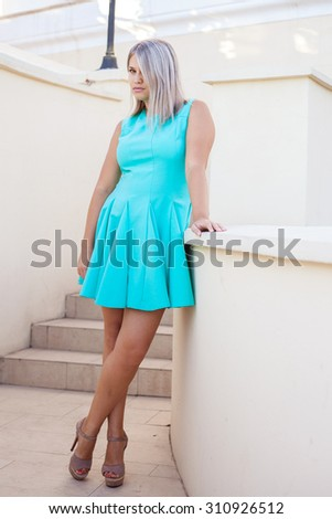 beautiful girl in a turquoise dress posing on the steps, outdoors