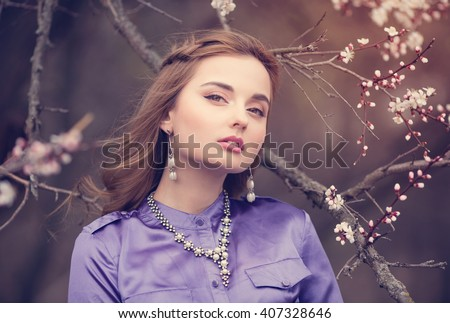 Beautiful girl in a vintage dress in spring garden among the blossoming cherry branches, covered with flowers, warmth, April, sunset, nature - stock photo