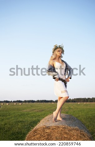Beautiful girl in a white dress near the hay  - stock photo