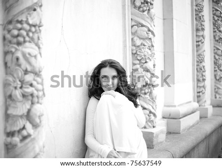 beautiful girl in a white dress near to white antique arches, black and white image - stock photo