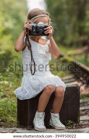 beautiful girl in a white dress sits on a vintage suitcase in a summer forest railway and pictures of forests around  - stock photo