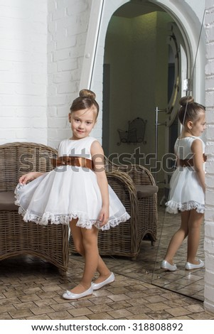 Beautiful girl in a white dress staying at the mirror - stock photo