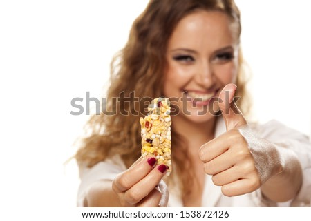 beautiful girl in a white shirt eats fruit bar and showing thumbs up - stock photo