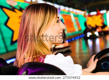 Beautiful girl in an electric bumper car in amusement park in typical German Dirndl dress with bright colours and lights in the background