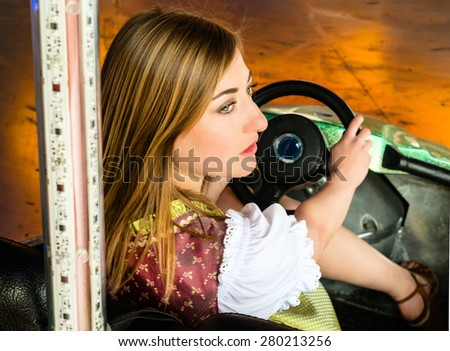 Beautiful girl in an electric bumper car in amusement park in typical German Dirndl dress with bright colours and lights in the background - stock photo