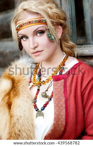 Beautiful girl in ancient  russian costume 8-9 century outdoor. Woman in the Russian national suit  - stock photo