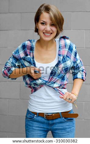 beautiful girl in anger tying his shirt on a light background
