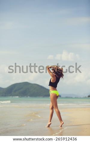 beautiful girl in bikini having fun running around dancing and posing on the beach in a swimsuit and shorts - stock photo